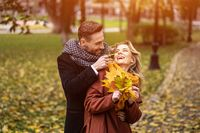 Happy young people in love, man hugging woman from behind stroking her cheek, happy couple walking in a autumn park wearing stylish coats and picking up fallen leaves. Family and people concept