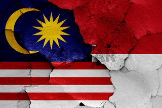 flags of Malaysia and Indonesia painted on cracked wall