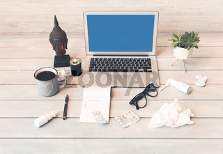 Laptop and medications of sick freelancer on wooden surface