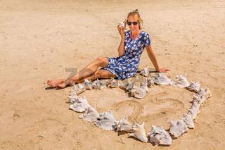 Woman with heart of karko shells on beach