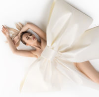 Nude girl on the floor with huge decorative bow
