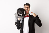 Funny young man in party suit, showing tongue and making grimaces, pointing at cute black dog in winter clothes, standing over white background