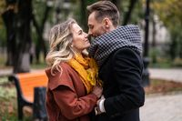 Passionate couple handsome guy hold his girlfriends hands and touching noses stand in fall town park wearing coats and scarfs. Smiling couple hugging in autumn park