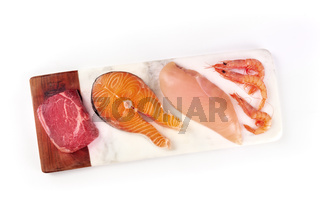 Fresh proteins. Raw beef meat, salmon fish, chicken breast, and shrimps, shot from the top with a place for text