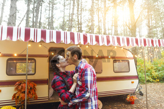 Portrait of romantic couple smiling while holding hands near house on wheels outdoors