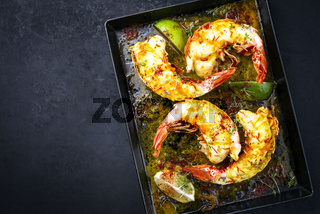 Traditional barbecue spiny lobster tail sliced and offered with saffron lemon sauce as top view on a metal tray with copy space left
