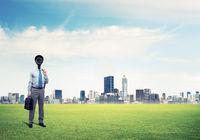 Camera headed man standing on green grass against modern cityscape