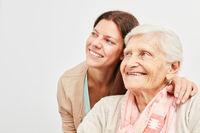 Frau und Senioren schauen zuversichtlich lächelnd