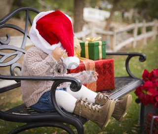Young Child Wearing Santa Hat Sitting with Christmas Gifts Outside.