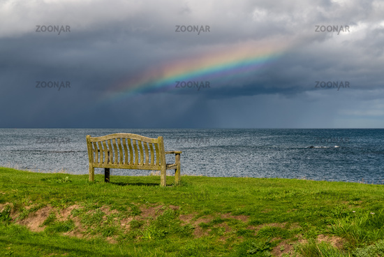 A bench with a Rainbow over the North Sea