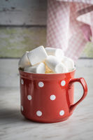 White sweet marshmallows candy in mug on kitchen table.