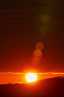 Rising of the sun in mountains, red sun disk rises from tops of mountain range
