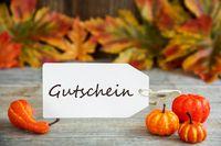 Label With Text Gutschein Means Voucher, Pumpkin And Leaves