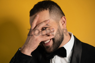 Shy young bearded man in tuxedo hide peeps out behind his hands on closed eyes. Handsome young smiling caucasian man isolated on yellow background