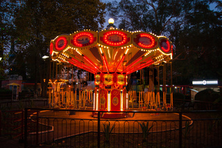 Carousel in bright lights on a dark summer south night against a background of trees and other attractions.