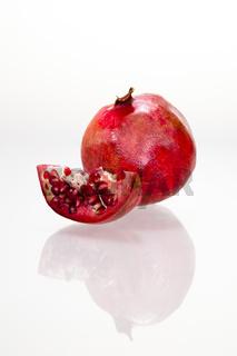 Angeschnittener Granatapfel mit Spiegelung vor weißem Hintergrund