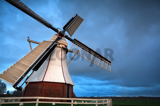 white Dutch windmill in sunset light