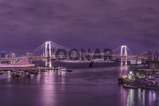 Circular highway leading to the Rainbow Bridge with Cargo and cruise ships moored or