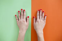 Woman with manicure placing hands over colorful background