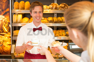 Shopkeeper in cafe giving cup of coffee to client