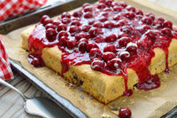 Cake with chocolate chips and cherry sauce