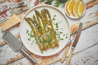 Delicious roasted asparagus served on white ceramic plate. With parmesan cheese, parsley and lemon.