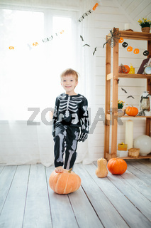 The little boy in a skeleton costume is ready to celebrate Halloween. Boy in a halloween dress-up room.