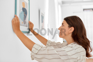 woman decorating home with picture in frame