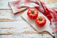 Top view of a white cutting board with a fresh juicy tomatoes on a wooden table