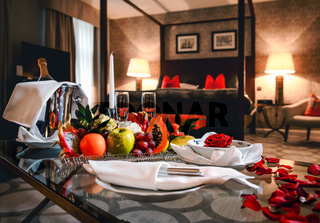 Luxury hotel room is ready for a romantic evening with champagne, fruits and rose petals