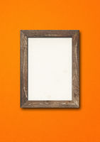 Old rustic wooden picture frame hanging on an orange wall