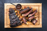 Traditional Barbecue burnt beef ribs St Louis style sliced and offered as top view on a rustic wooden board