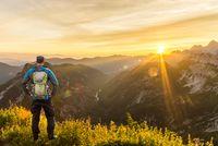 Man reaching summit enjoying amazing sunrise in the mountains. Backlight Sunlight with beautiful lens flares and sunbeams. Julian Alps, Triglav National Park, Slovenia, Mountain Slemenova, Sleme.