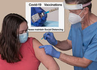 Senior male doctor vaccinating a young woman in clinic for coronavirus