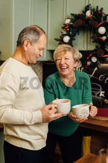 Photo of 60s elderly couple enjoying life at the kitchen with mugs of coffee. st valentines day of old couples in love. stop ageism discrimination