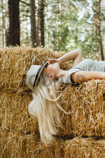 Young adult blond woman in a hat lying hay stack, selective focus