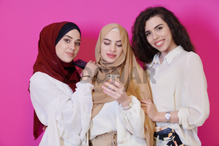 muslim women using mobile phone isolated on pink