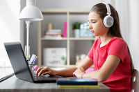 girl in headphones with laptop computer at home