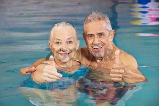 Paar Senioren hält Daumen hoch im Schwimmbad