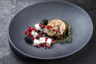 Gravy Greek lamb roast with feta cheese and fruits as minimalistic gourmet meal as closeup in a modern design plate