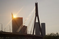 Suspension bridge over the Daugava River on a sunset on background of the modern part of the city. L