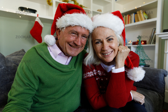 Portrait of senior couple in santa hat smiling while sitting on couch at home