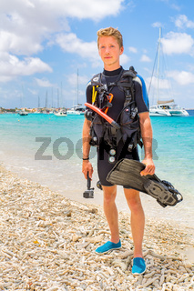 Caucasian diver standing on beach near sea and boats