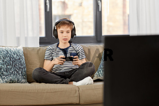 boy with gamepad playing video game at home