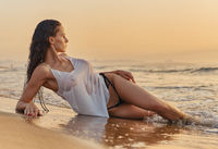 Sexy woman posing on beach near the sea at sunrise