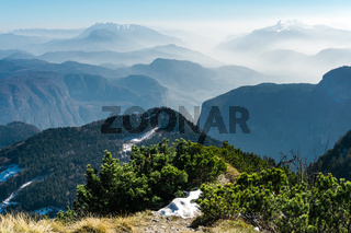 Spectacular view of mountain ranges silhouettes and fog in valleys. View from Top of Mount Corno di Tres, Tresner Horn to Cima Paganella. Trentino, South Tyrol, Alps, Italy.
