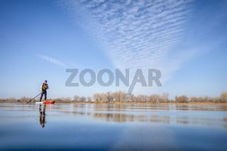 senior male paddling stand up paddleboard