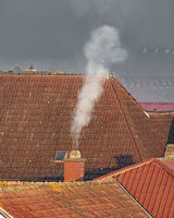 Roofs of an old village with a smoking chimney and copyspace