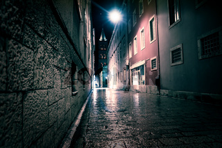 Blue ligntened cobbled street with bell tower at the end of the street, Zadar, Croatia