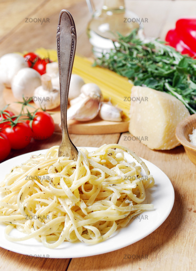 Pasta in the white plate on the wooden table